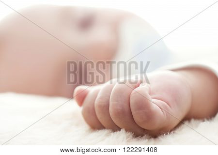 Closeup portrait of cute newborn baby sleepinginnocent child soft focus hope and help concept.Selective focus on baby hand.