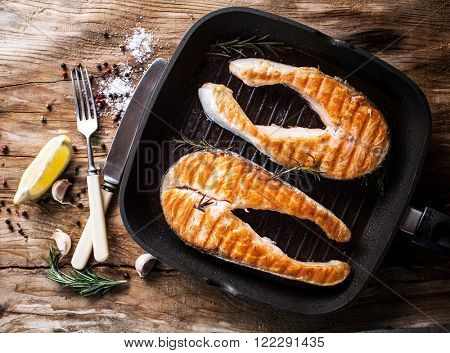 grilled salmon steak on grill pan on wooden background