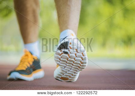 A person running outdoors on a sunny day. Only the feet are visible. The person is wearing black running shoes.Exercise fitness and healthy lifestyle.