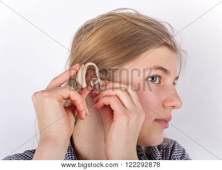 The blond Girl inserting her hearing aid.