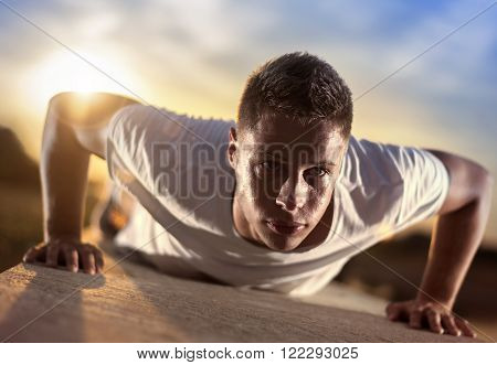 Picture of a young athletic man doing push ups outdoors.Keeping fit for a healthy mind and body. Fitness and exercising outdoors urban environment.