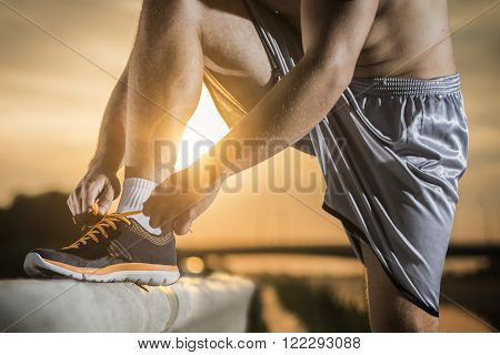 Man tying jogging shoes.A person running outdoors on a sunny day. The person is wearing black running shoes.Focus on a side view of two human hands reaching down to a athletic shoe.