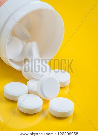 White tablets spilling out of white plastic bottle over yellow background