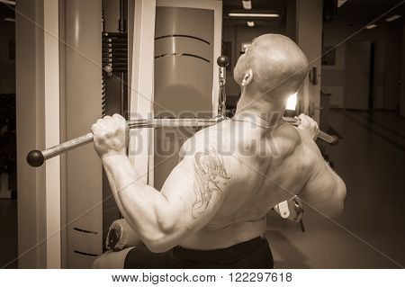 Athlete in the gym making vertical thrust. The power to exercise the muscles of the back. Photos for sporting magazines, posters and websites.