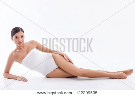 I like caring of my skin. Portrait of attractive girl lying and touching her legs gently. The lady is looking at camera and smiling. Isolated on white background