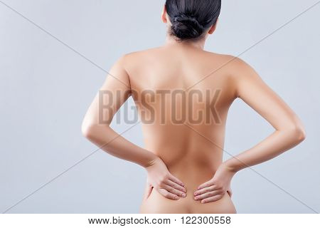 Cheerful fit girl is making massage for herself. Her back hurts. She is standing and touching her loins. Isolated and copy space in left side
