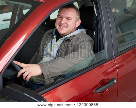 Young fat man behind wheel. Smiling Caucasian man