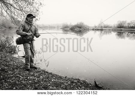 Fisherman on the autumn background. Fisherman in his hand holding spinning. Fishing, spinning reel, fish, Breg rivers. - The concept of a rural getaway. Article about fishing.