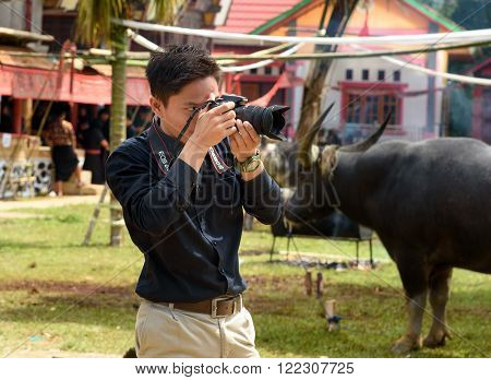 Photographer In Black At Funeral Ceremony. Tana Toraja