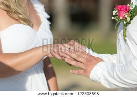 Groom holding bride's hand in outdoors wedding, holding hands newlyweds.