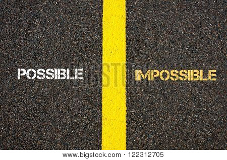 Antonym concept of POSSIBLE versus IMPOSSIBLE written over tarmac, road marking yellow paint separating line between words