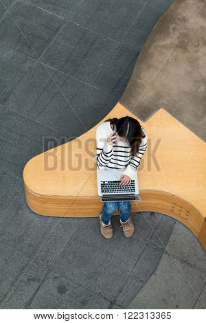 Top view of woman talk to mobile phone and use of notebook computer