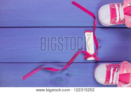 Pregnancy test with positive result and shoes for newborn on purple boards, concept of extending family and expecting for baby, copy space for text or inscription
