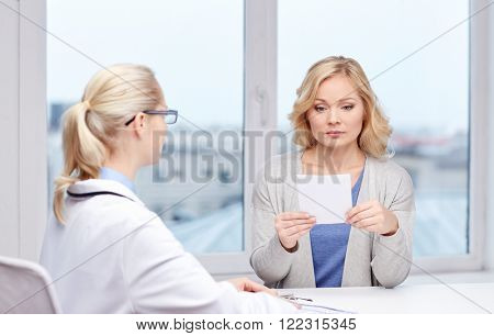 medicine, health care, meeting and people concept - doctor giving medical prescription or certificate to woman at hospital