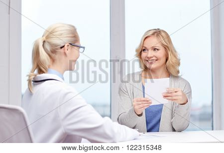 medicine, health care, meeting and people concept - smiling doctor giving medical prescription or certificate to woman at hospital