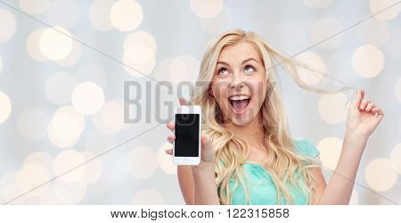 emotions, expressions, technology and people concept - smiling young woman or teenage girl showing blank smartphone screen over holidays lights background