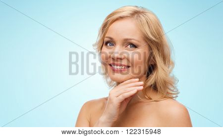 beauty, people and skincare concept - smiling middle aged woman with bare shoulders touching face over blue background