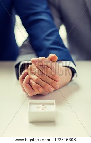 people, homosexuality, same-sex marriage and love concept - close up of happy male gay couple holding hands and wedding rings in box on table