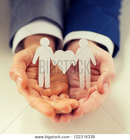 people, homosexuality, same-sex marriage and love concept - close up of happy male gay couple holding paper cutout love symbol
