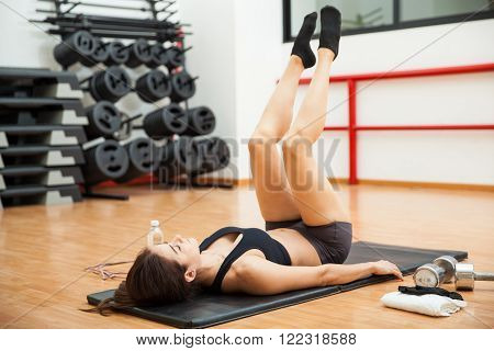 Beautiful young woman doing leg raises and working on her abs at the gym