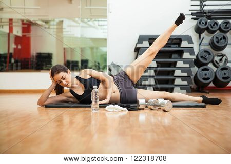Pretty young athletic woman doing side crunches and working out at the gym