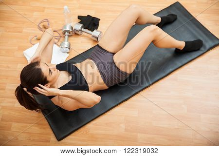 Young athletic brunette doing crunches at the gym and strengthening her abs, as seen from above