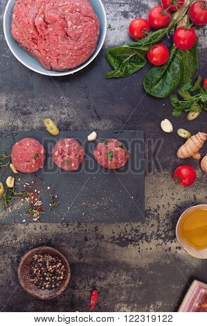 Raw meatballs with spices. Minced meat mixture for meatballs and ingredients on dark background. Top view, vintage toned image, blank space