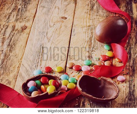Easter chocolate eggs candy multicolored red silk ribbon on a wooden table