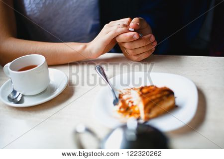 Couple in a cafe held by the hand, a piece of cake  at foreground