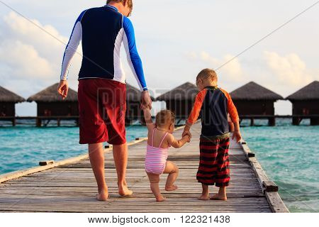 father with kids walking on tropical resort in Maldives
