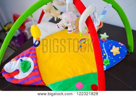 Baby cot with colorful toys hanging in natural light