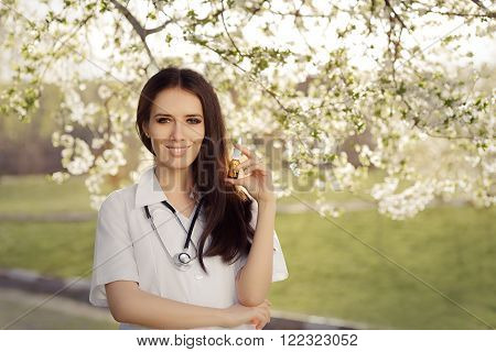 Spring Woman Doctor Smiling and Holding Respiratory Spray  - Portrait of female medical professional with a breathing remedy in springtime decor