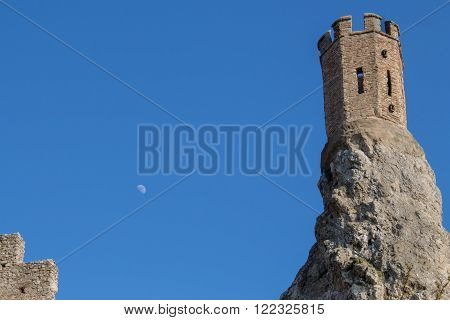Part of ruins of castle Devin in Slovakia. Maiden tower built on the edge of a high rock. Bright blue sky with moon.