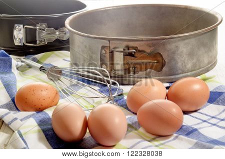 free range eggs on a kitchen towel whisk and old baking tin