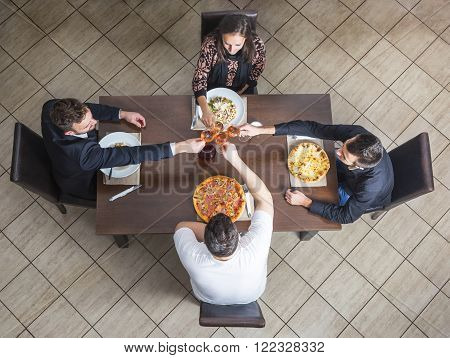 Upper view of four friends clinking wine glasses at a table in a restaurant.