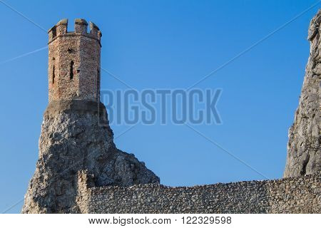 Rocks of the former fortress with a Maiden Tower part of ruins of castle and fortress Devin in Slovakia. Bright blue sky.