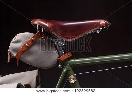 Vintage road bicycle saddle with under saddle bag, isolated on black.
