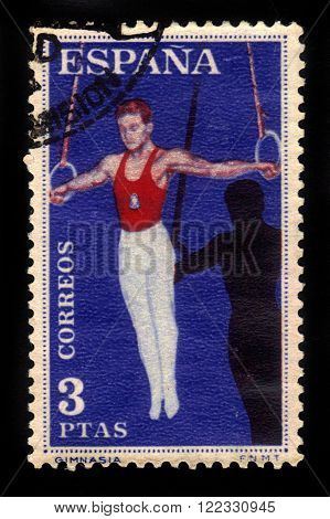 SPAIN - CIRCA 1960: a stamp printed in Spain shows gymnastics, exercise on the rings, circa 1960