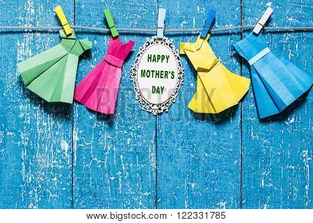 The idea of design for Mother's Day: dresses from paper in the technique of origami on a rope with clothespins and the inscription: Happy Mother's day