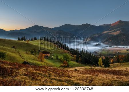 Carpathian Mountains. Moonlit Night in the mountains, the village on the hill in the fog.