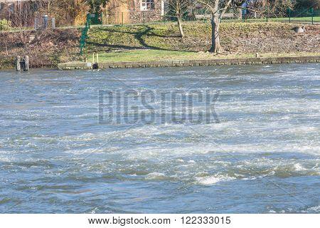 Flooded embankment in heavy rain in Essen Werden in Germany.