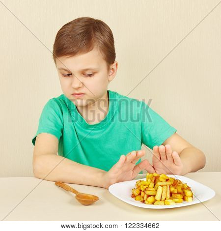 Little boy does not want to eat a fried potatoes