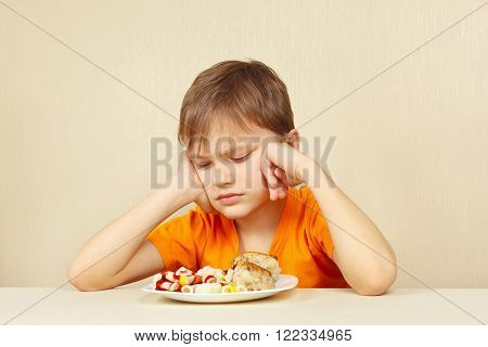 Little displeased boy does not want to eat a pasta with cutlet
