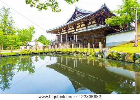 NARA, JAPAN - JUNE 24, 2015: Front entrance of Sangatsu-do Hall reflected in the front pond on a sunny morning in the Todai-ji temple complex at Nara Japan. Horizontal