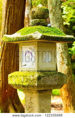 NARA, JAPAN - JUNE 24, 2015: Old traditional stone lantern covered in green moss among trees at Todai-ji temple complex in Nara Japan