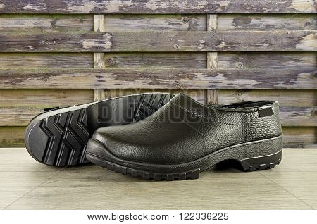 Pair of new shiny black shoes or clogs on a wooden table. In the background an old unpainted brown fence.