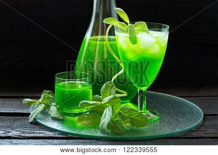 Drink with tarragon and mint in a carafe and glass cocktail with soda and ice in a wineglass on a glass tray. Selective focus