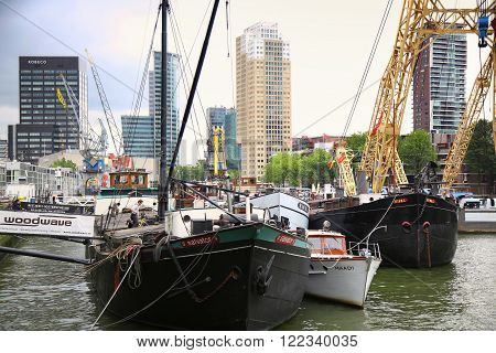 ROTTERDAM THE NETHERLANDS - 18 AUGUST: Old cranes in Historical Leuvehaven Rotterdam's oldest sea port. Harbor and modern apartment buildings in Rotterdam Netherlands on August 182015.