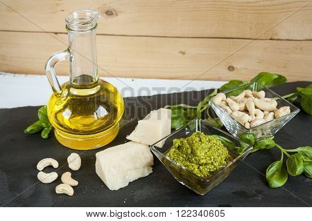 Basil pesto fresh basil leaves parmigiano cheese olive oil and cashew seeds on black stone background. Mediterranean food on black  stone board