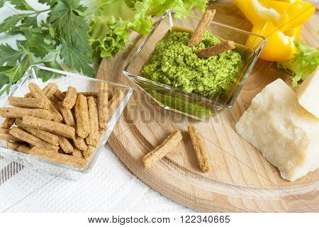 Basil pesto with bread rusks parmigiano cheese fresh yellow pepper lettuce leaves parsley on wooden board and napkin background